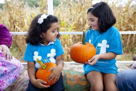 Aanya Baid, age 4, of Norwood, on left, and Arya Gurkar, age 5, of Norwood with their pumpkins on the hayride from the pumpkin patch at Ward's Berry Farm on South Main Street in Sharon.
